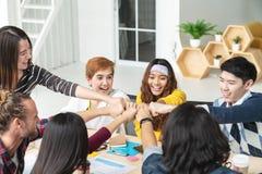 不同种族的年轻队堆一起递作为被信任的团结和配合在现代办公室 免版税库存图片
