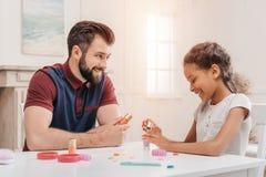 不同种族的父亲和女儿绘画在家一起钉牢 免版税库存图片