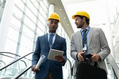 不同种族的男性建筑师谈论在数字片剂在办公室自动扶梯 免版税库存图片
