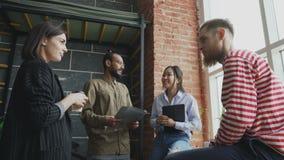 不同种族的起始的队是群策群力和谈论新的想法在现代办公室,当站立近的窗口时 影视素材