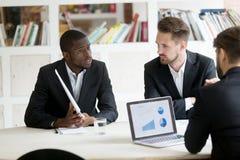 不同种族的雇员谈论经营计划与CEO 免版税库存照片
