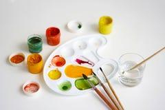不同颜色、刷子、塑料调色板和一杯树胶水彩画颜料水 免版税库存图片