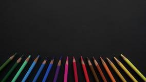 不同颜色木学校铅笔位于黑表面 与色的铅笔的停止运动动画 影视素材