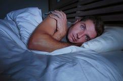 不安定的担心的年轻可爱的人醒在说谎在床上的晚上失眠与眼睛宽被打开的遭受的失眠睡觉diso 免版税库存照片