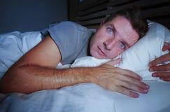 不安定的担心的年轻可爱的人醒在说谎在床上的晚上失眠与眼睛宽被打开的遭受的失眠睡觉diso 免版税库存图片