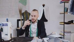 不对称的 疲乏的时装设计师和裁缝工作书桌的有织品的在演播室 工作日的完成 股票视频