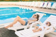 不尽的夏天!逗人喜爱的放松在sunbed的婴孩和母亲 免版税库存照片