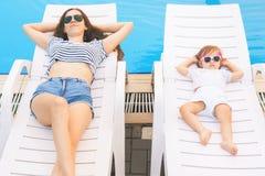 不尽的夏天!逗人喜爱的放松在sunbed的婴孩和母亲 库存图片