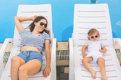 不尽的夏天 逗人喜爱的放松在sunbed的婴孩和母亲 免版税图库摄影