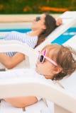 不尽的放松在sunbed的夏天逗人喜爱的婴孩在水池,手段附近 库存图片