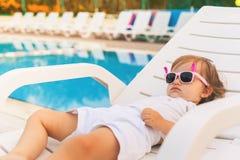 不尽的放松在sunbed的夏天逗人喜爱的婴孩在水池,手段附近 库存照片
