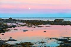 不尽的极性天在北极 在白海的岸在低潮期间的 与云彩的剧烈的天空在晚上 免版税库存图片