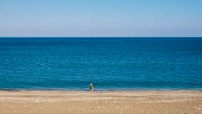 不尽的海和tr的一个小遥远的剪影的天际 免版税库存照片