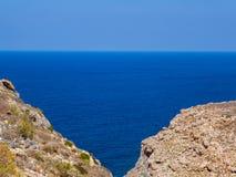 不尽的蓝色海看法,两岩石小山在前景见面 免版税库存照片