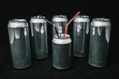 不平等和不公道 在小罐头附近的大铝罐 有保镖概念的上司 休息的主要人 库存照片