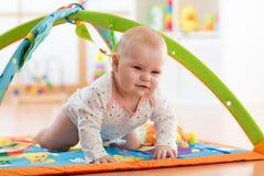不快乐的七个月爬行在五颜六色的playmat的女婴 免版税库存照片