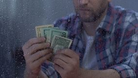 不快乐的中年男性藏品美元现金,不足的预算,失业 股票录像