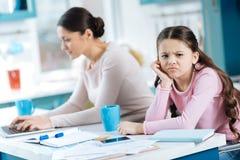 不快乐的乏味女孩和她的妈妈工作 免版税库存图片