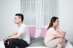年轻不快乐的亚洲夫妇紧接坐沙发在家 免版税库存图片
