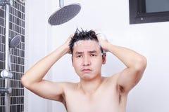 不快乐的人采取一根阵雨和洗涤的头发在bathroo 免版税库存图片