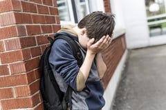 不快乐的前青少年的男孩在学校 免版税库存图片