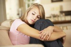 不快乐的十几岁的女孩在家坐沙发 库存照片