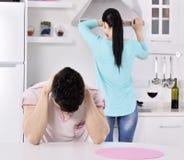 不快乐的夫妇红色wvne在厨房里 免版税库存图片