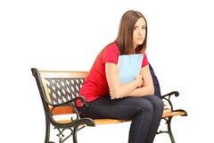 不快乐的女学生坐与笔记本的一个长木凳 免版税图库摄影