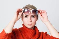 不快乐的女孩佩带的冬天毛线衣尝试的太阳镜 免版税库存图片