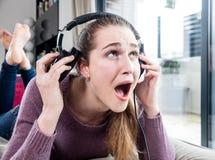 不快乐的女孩在痛苦中尖叫在去除她的耳机在家 库存照片