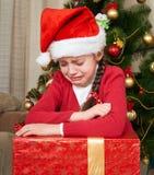 不快乐的女孩棚子在圣诞树附近撕毁,穿戴在红色和圣诞老人帽子 库存照片