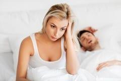 不快乐的妇女在与打鼾的睡觉的人的床上 库存图片