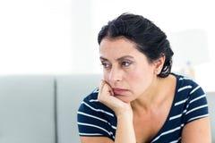 不快乐的妇女坐长沙发 免版税库存照片