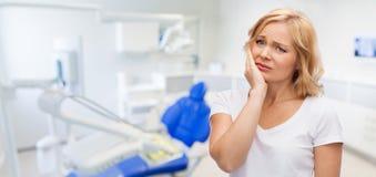 不快乐的妇女遭受的牙痛在牙齿办公室 免版税库存图片