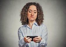 不快乐的妇女,懊恼由某人她的手机的,当发短信时 库存图片