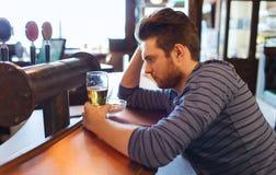 不快乐的孤独的在酒吧或客栈的人饮用的啤酒 免版税图库摄影