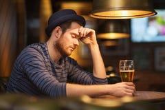 不快乐的孤独的在酒吧或客栈的人饮用的啤酒 免版税库存图片