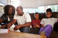 不快乐的家庭坐看票据的沙发 库存照片