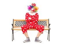 不快乐的小丑坐一个长木凳 免版税库存照片