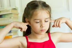 不快乐的小女孩画象有闭合的耳朵的 免版税图库摄影