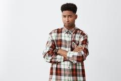 不快乐的年轻可爱的黑皮肤的人画象有卷发的在偶然方格的衬衣横穿手上,看 免版税库存照片