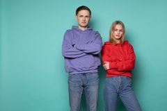 不快乐的恼怒的人男人和妇女便服的,一起站立对蓝色墙壁在演播室 免版税库存照片