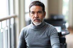 不快乐的恼怒的成熟亚裔人画象有看与消极可疑的时髦的短的胡子的cemera 免版税库存图片