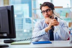 不快乐的恼怒的电话中心工作者挫败与工作量 免版税库存图片