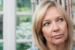 不快乐的成熟妇女首肩画象在家 免版税库存照片