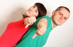 不快乐的显示拇指的妇女和人下来 免版税库存照片