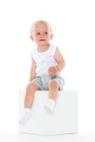 不快乐的男婴坐立方体。 库存照片