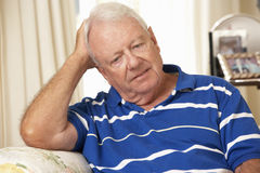 不快乐的退休的老人在家坐沙发 库存图片