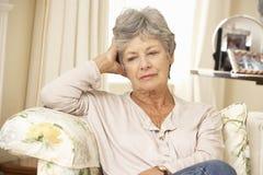 不快乐的退休的资深妇女在家坐沙发 图库摄影