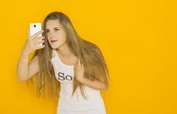 不快乐的年轻可爱的妇女非常使某事惊奇在她的智能手机 图库摄影